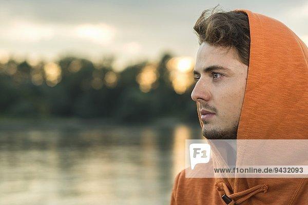 Junger Mann mit orangefarbenem Kapuzenoberteil
