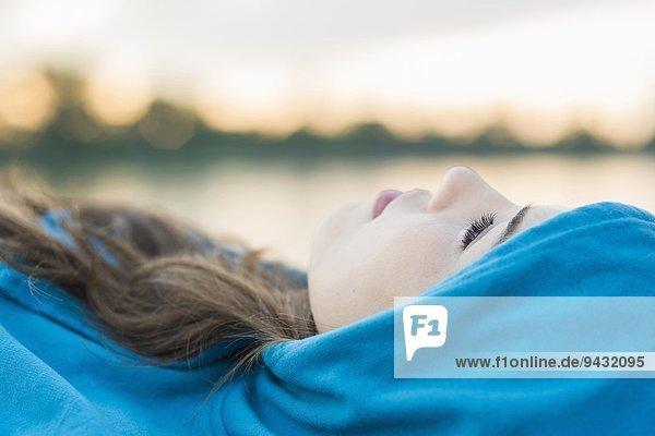Junge Frau in blauem Kapuzenoberteil liegend