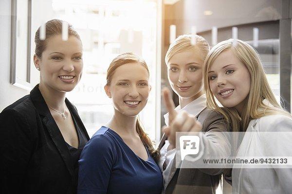Geschäftsfrauen schauen und zeigen auf Glas