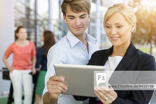 Geschäftsmann und Geschäftsfrau tauschen Informationen auf digitalen Tabletts aus
