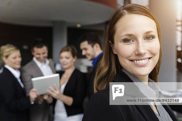 Lächelnde Geschäftsfrau  Kollegen im Hintergrund mit digitalem Tablett