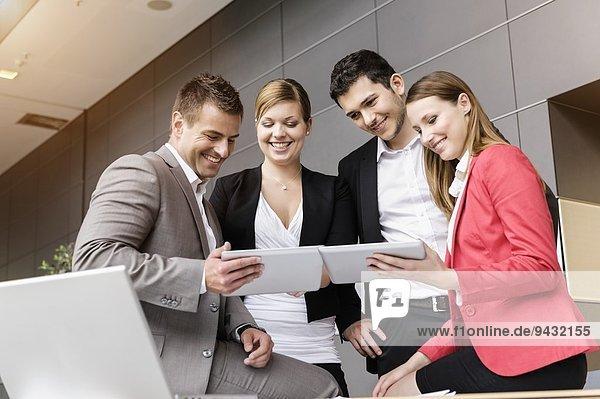 Geschäftsleute tauschen Informationen auf digitalen Tabletts aus
