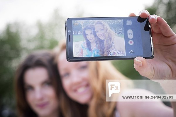 Close up of two young female friends taking selfie on smartphone in park