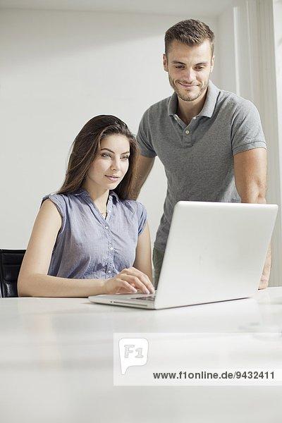 Junges Paar bei der Arbeit am Laptop