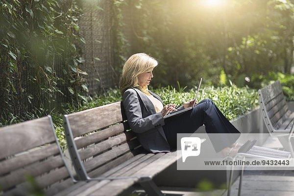Reife Geschäftsfrau auf der Bank sitzend mit Laptop