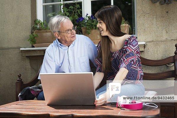 Junge Frau mit Laptop mit Großvater