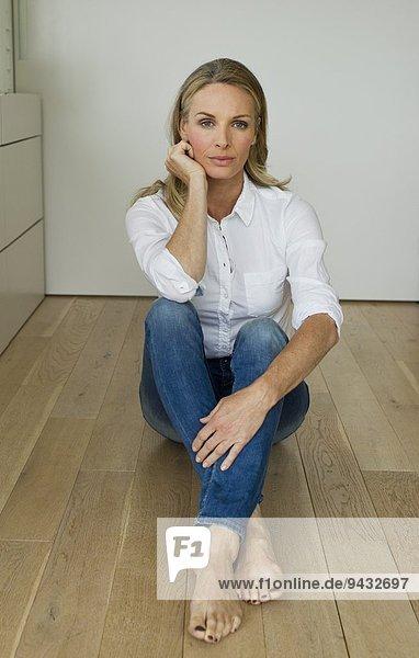 Mature woman sitting on wooden floor  portrait