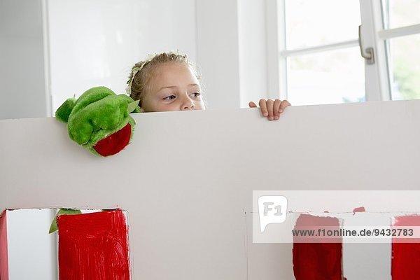 Mädchen blickt über das Spielzeugtheater mit Puppe
