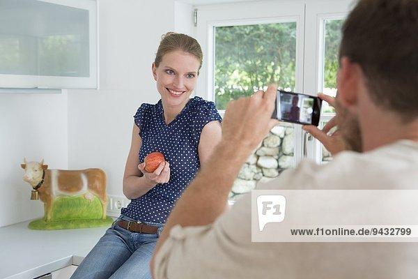 Mann fotografiert Frau mit Fotohandy