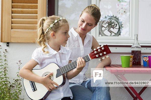 Mädchen spielt Gitarre mit Mutter
