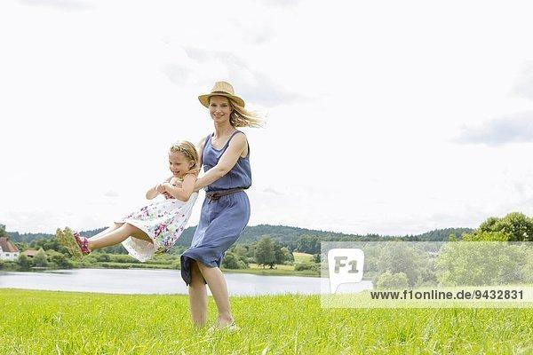 Mutter hebt Tochter im Feld auf