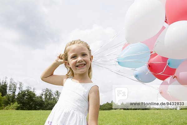Mädchen mit einem Haufen Luftballons