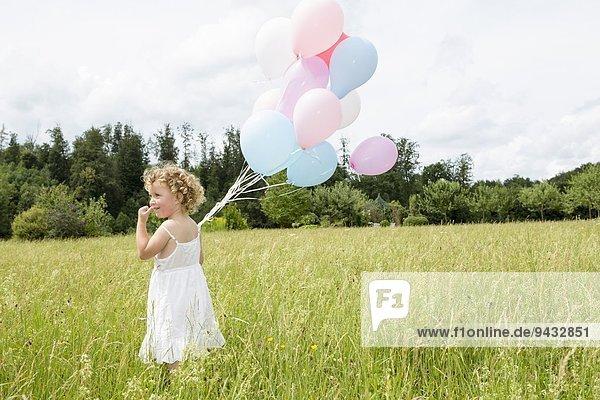 Junges Mädchen mit Luftballons im Feld