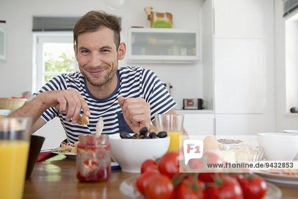 Mittlerer Erwachsener Mann beim Essen am Küchentisch