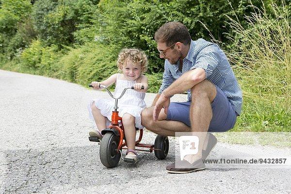 Mädchen auf dem Dreirad mit Vater