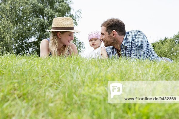 Mutter und Vater mit Tochter auf Gras