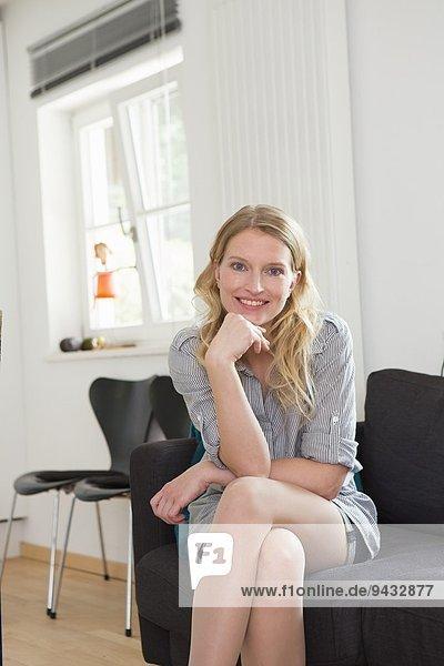 Mittlere erwachsene Frau auf Sofa sitzend  Portrait