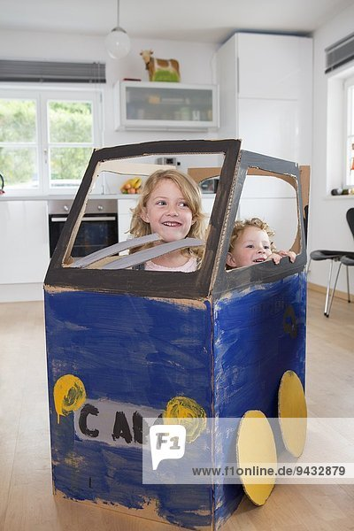 Zwei Mädchen im hausgemachten Spielzeugauto