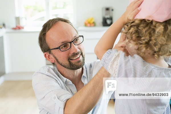 Mädchen versucht auf Papier Krone mit Vater