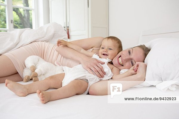 Mutter und Tochter auf dem Bett liegend