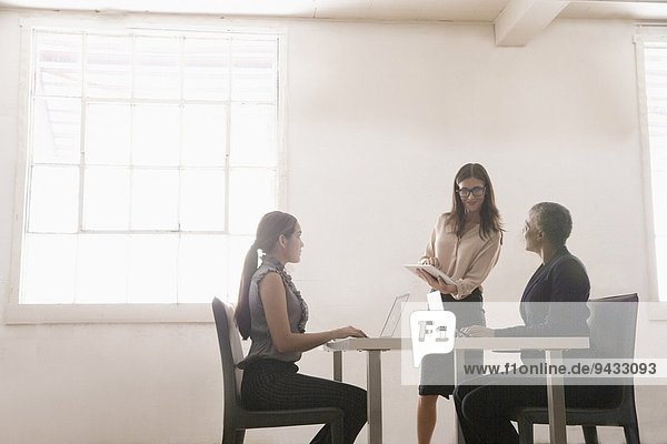 Businesswomen sitting at table  manager talking