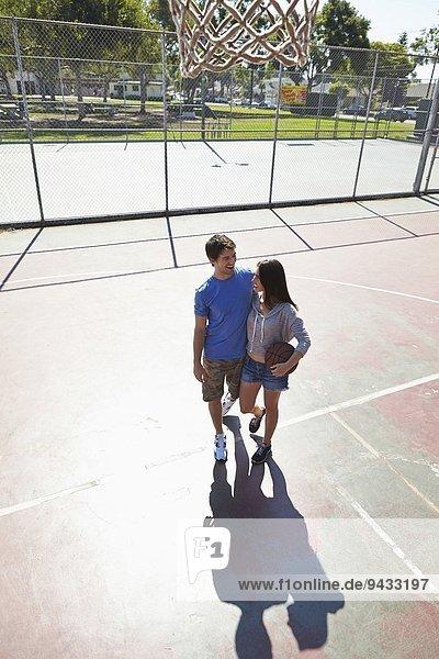 Junge Paare umarmen sich auf dem Basketballplatz
