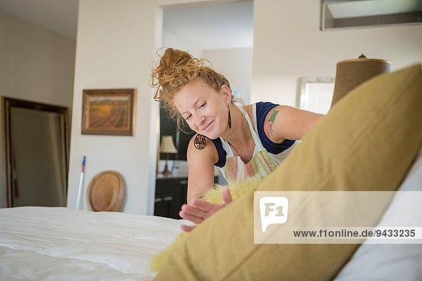 Junge Frau reinigt Schlafzimmer mit grünen Reinigungsmitteln