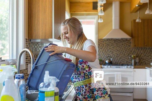 Junge Frau reinigt Küche mit grünen Reinigungsmitteln
