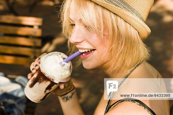 Junge Frau trinkt Frappe mit Strohhalm im Park