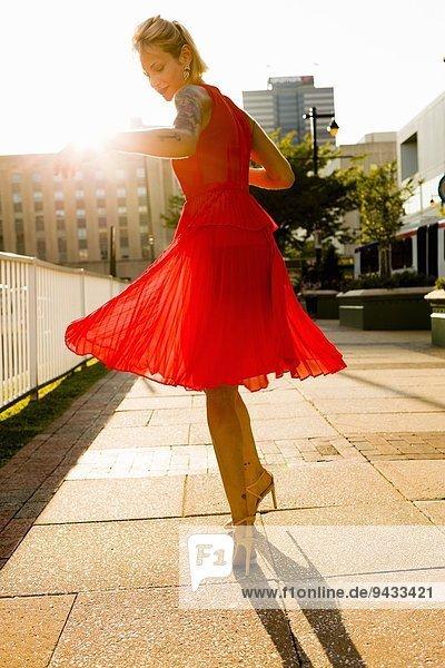 Junge Frau  die im roten Kleid wirbelt