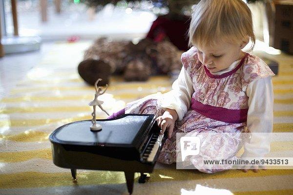 Weibliches Kleinkind auf dem Wohnzimmerboden sitzend  spielend mit Spielzeug-Klavierspieluhr zu Weihnachten