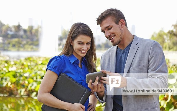 Businessman and woman using smartphone  Echo Park  Los Angeles  California  US
