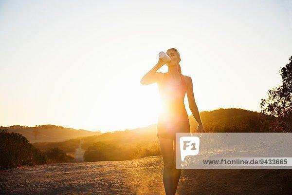 Joggerin beim Trinken im Sonnenlicht  Poway  CA  USA