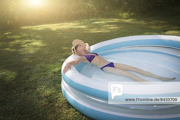 Reife Frau entspannt im Planschbecken