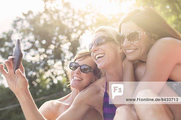 Drei reife Frauen in Badebekleidung  die sich selbst porträtieren.