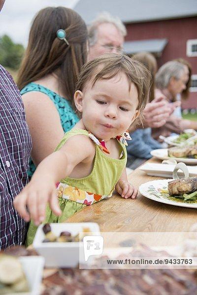 Kleinkind pflückt Oliven vom Teller beim Familienessen  im Freien
