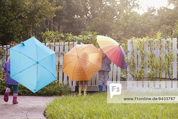 Junge und zwei Schwestern beim Spielen im Garten mit Regenschirmen