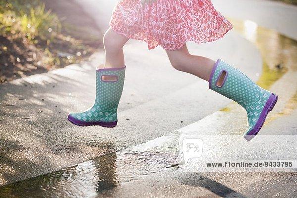 Taille nach unten Ansicht des Mädchens springen Pfützen auf regnerischer Straße