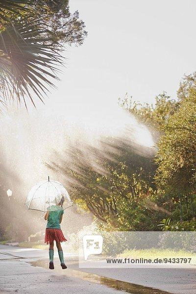 Rückansicht des Mädchens  das den Regenschirm hochhält und Pfützen auf der Straße springt.