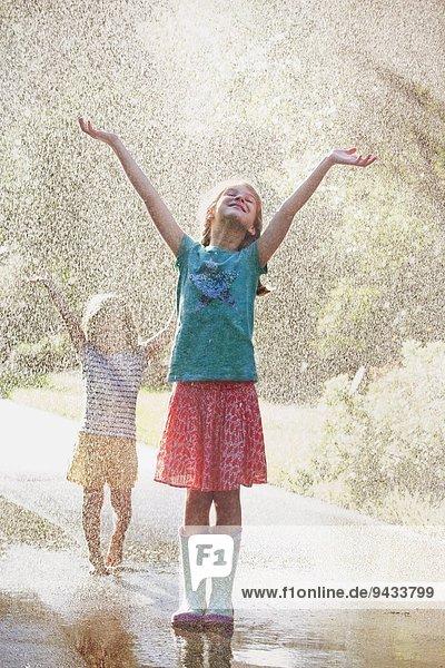 Zwei Mädchen mit offenen Armen stehend im Wasserstrahl auf der Straße