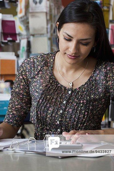 Verkäuferin mit Taschenrechner im Schreibwarengeschäft