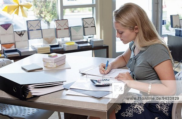 Female sales assistant doing paperwork in stationery shop