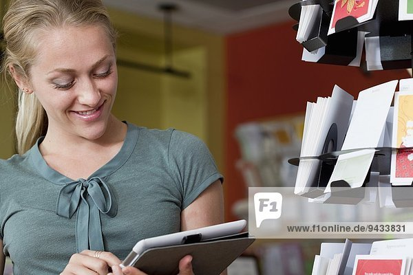 Female sales assistant using digital tablet in stationery shop