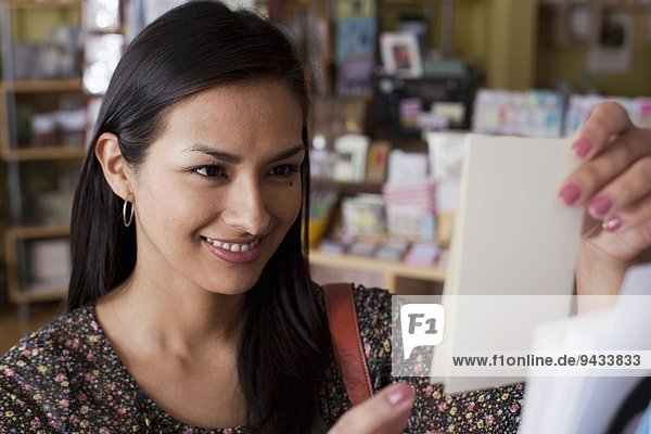 Female customer selecting greetings card in stationery shop