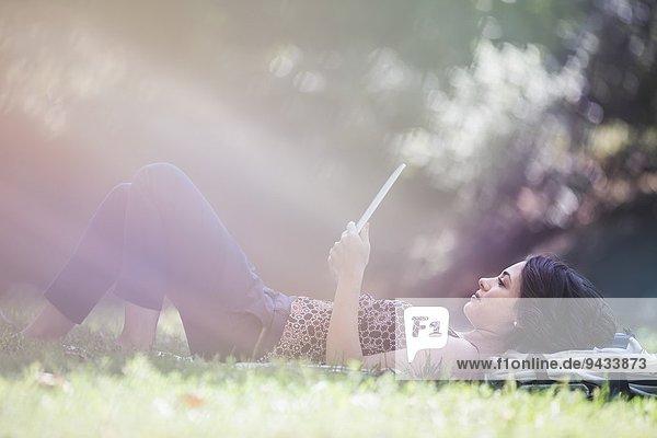 Junge Frau entspannt im Stadtpark beim Lesen des digitalen Tabletts Junge Frau entspannt im Stadtpark beim Lesen des digitalen Tabletts
