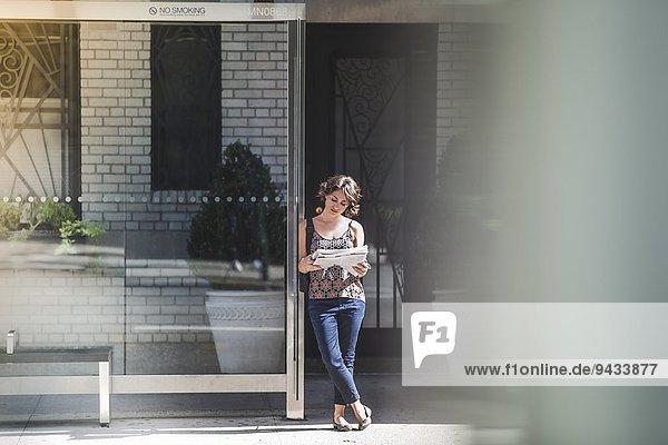 Junge Frau an der Bushaltestelle Zeitung lesen und auf den Bus warten  New York  USA