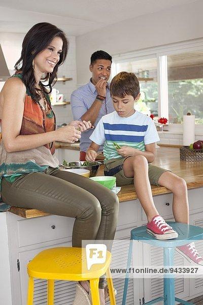 Junge sitzt auf der Küchentheke mit Mutter und Vater