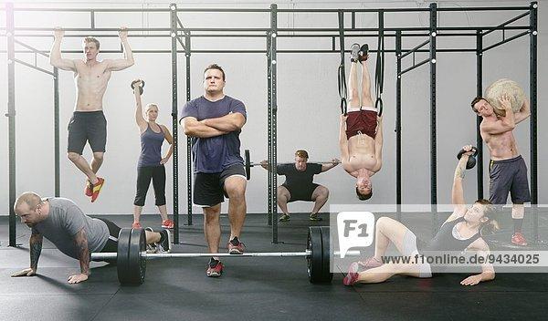 Porträt von acht männlichen und weiblichen Crossfit-Kollegen  die im Fitnessstudio tätig sind.