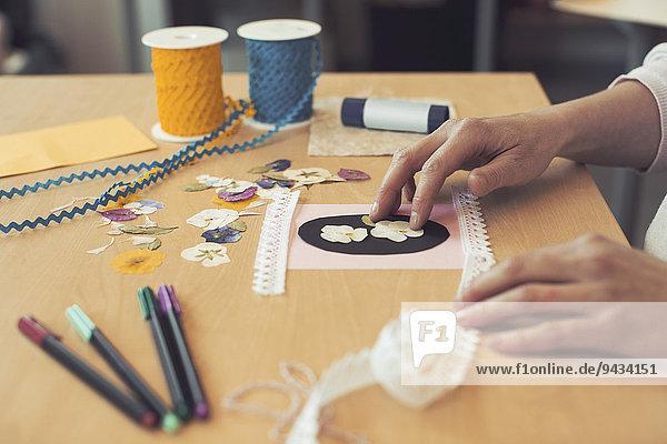 Abgeschnittenes Bild einer Frau  die ein Kunstprodukt auf dem Tisch herstellt.