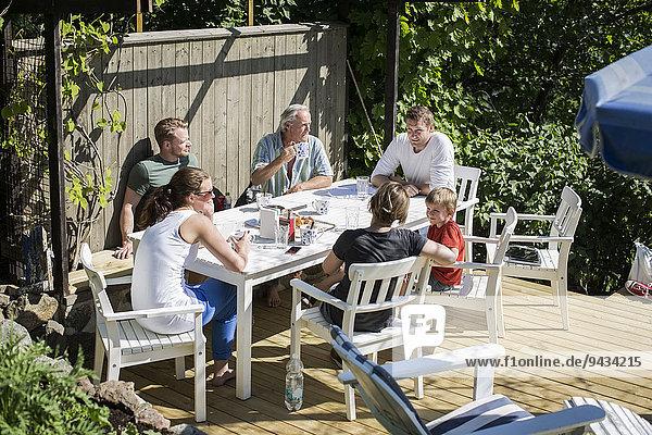 Familie und Freunde beim Frühstück im Hof
